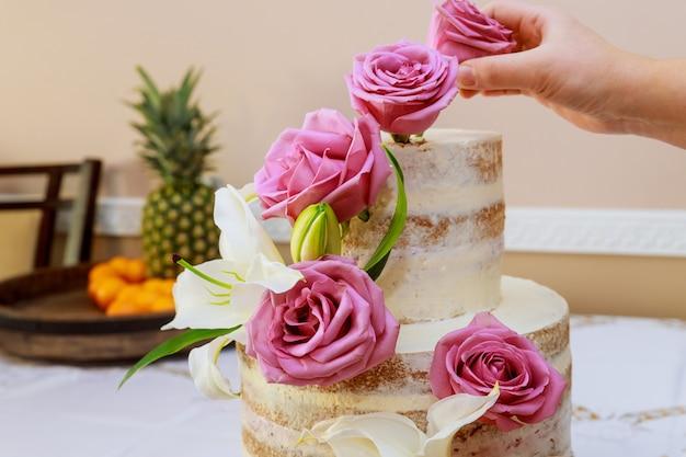 Vrouw die naakte cake met bloemen verfraait