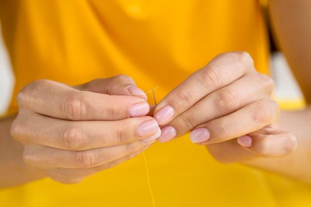 Vrouw die naald en draad gebruikt