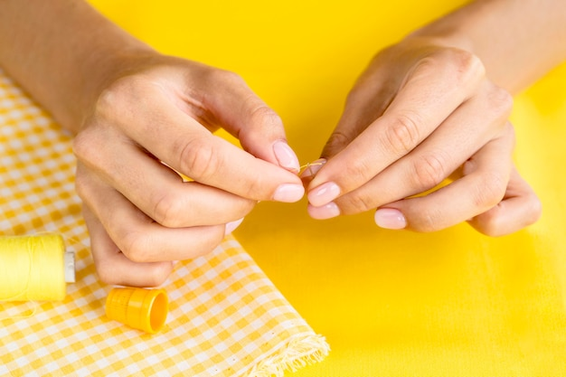 Vrouw die naald met draad voor het naaien voorbereidt