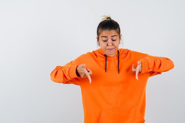 Vrouw die naar beneden wijst in een oranje hoodie en er gefocust uitziet