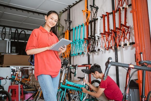 Vrouw die naar de camera lacht terwijl ze een digitale tablet gebruikt die tegen een fietsenwinkel staat