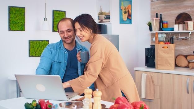 Vrouw die naar de laptop van de echtgenoot kijkt terwijl hij in de keuken werkt. vriendin bedrijf kopje koffie. man en vrouw koken recept eten. gelukkig gezond samen levensstijl. familie op zoek naar online mij