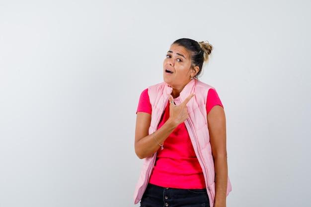 Vrouw die naar de rechterbovenhoek wijst in t-shirt, vest en aarzelend kijkt