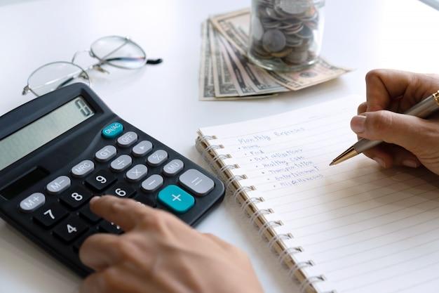 Vrouw die naar huis maandelijkse uitgaven in notitieboekje schrijven terwijl het gebruiken van calculator op bureau. kopieer ruimte, close-up.