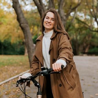 Vrouw die naast haar fiets loopt
