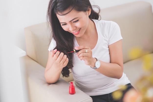 Vrouw die nagellak toepast in haar spijker