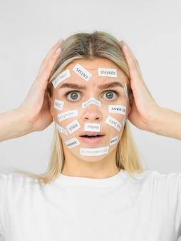 Vrouw die ncov titelstickers op haar gezicht heeft