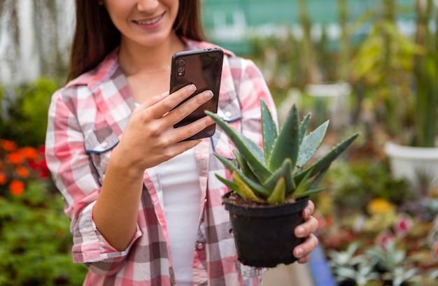 Vrouw die nemend beeld van installatie met telefoon in serre glimlachen