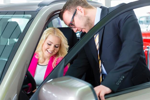 Vrouw die nieuwe auto in autohandel drijven