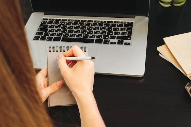 Vrouw die nota's in blocnote in een bureau maakt