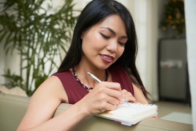 Vrouw die nota's in blocnote neemt