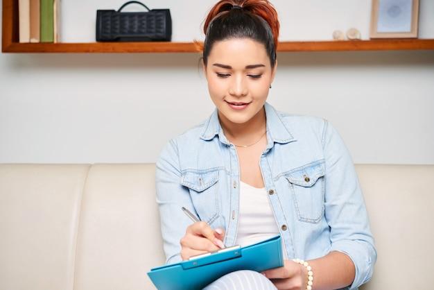 Vrouw die nota's in document maakt