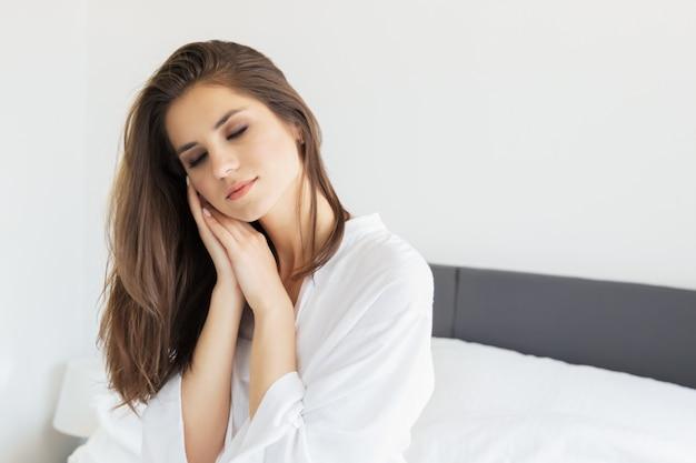 Vrouw die ochtend van het wekken in een zacht sneeuwwit bed genieten.