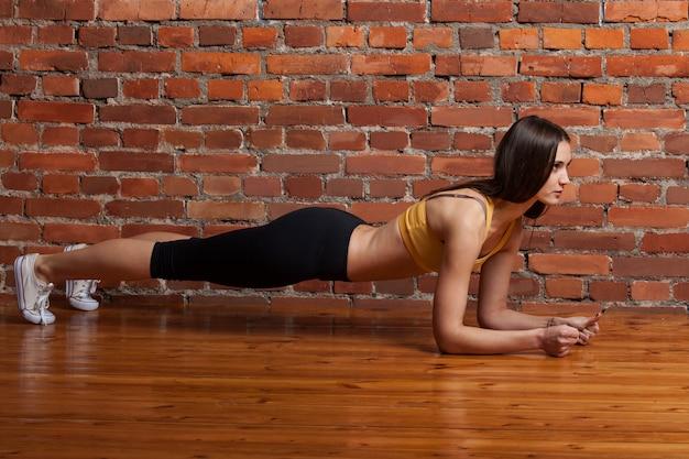 Vrouw die oefening op een bakstenen muurachtergrond doet