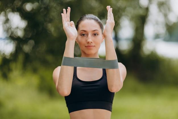 Vrouw die oefening voor haar handen met een band in het park doet openlucht.