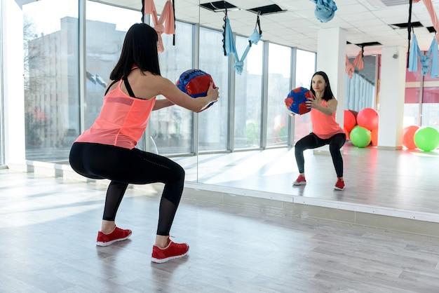 Vrouw die oefeningen met bal vóór spiegel in gymnastiek maakt