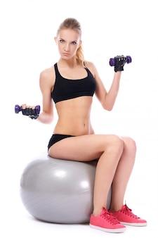 Vrouw die oefeningen met dumbells op geschiktheidsbal doet