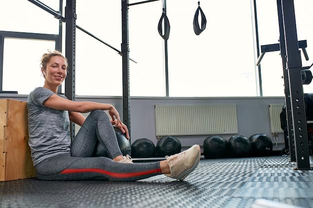 Vrouw die oefeningen met fitball in de klasse van de geschiktheidsgymnastiek doet. betrekkende kern buikspieren. beeldconcept gezonde levensstijl voor vrouwen.
