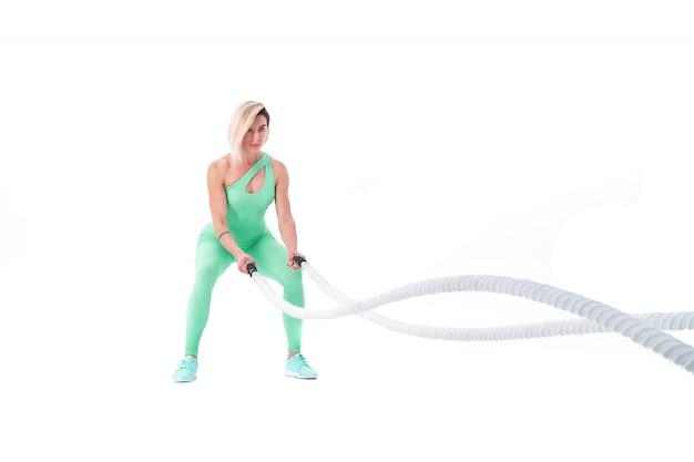 Vrouw die oefeningen met gevechtskabel doet op wit