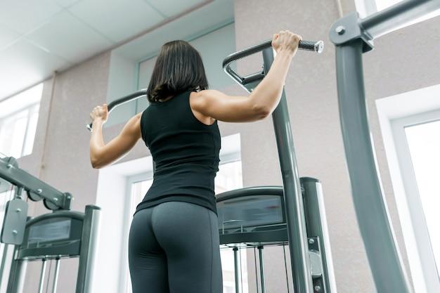 Vrouw die oefeningen voor de rug op geschiktheidsmachine doet in de gymnastiek
