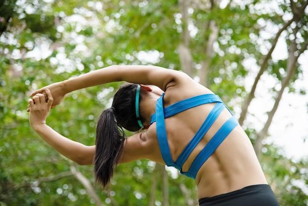 Vrouw die oefeningskostuum draagt, zich uitrekt terug en lichaam door handen op te heffen en uit in de lucht te reiken