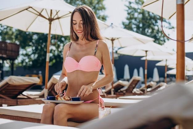 Vrouw die oekraïense syrnyki eet bij het zwembad