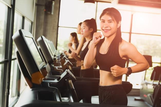 Vrouw die of op tredmolens in moderne sportgymnastiek loopt jogt. oefening en sportconcept.
