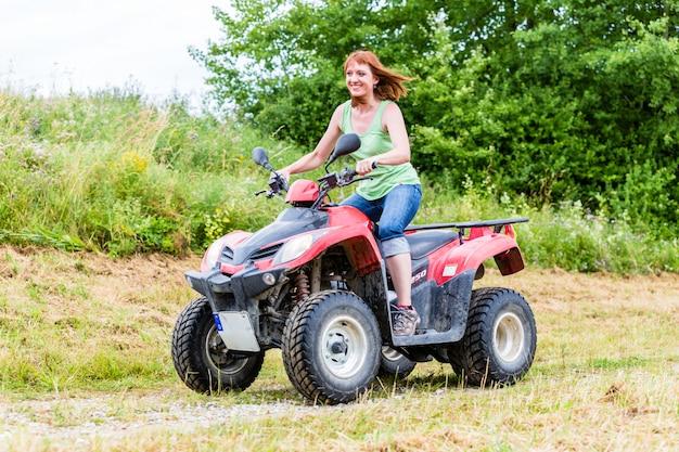 Vrouw die off-road met vierlingfiets of atv drijft