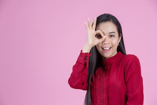 Vrouw die ok handteken over oog toont