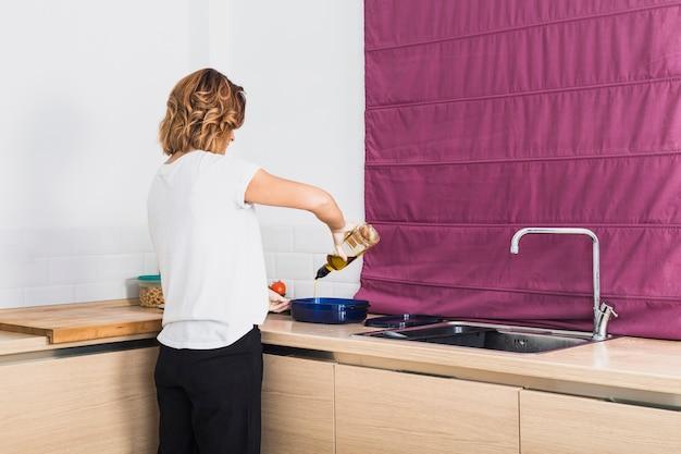 Vrouw die olie in container zet bij keuken
