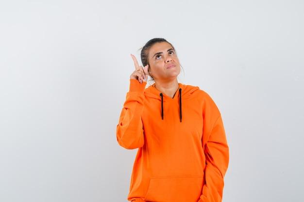 Vrouw die omhoog wijst in oranje hoodie en er hoopvol uitziet