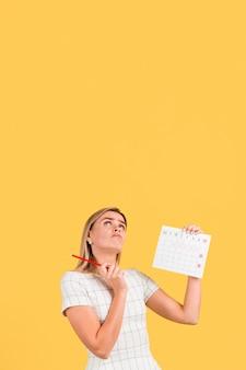 Vrouw die omhooggaand en menstruatiekalender met exemplaarruimte kijkt kijkt