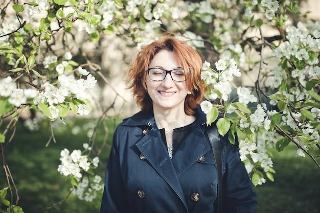 Vrouw die onder bloeiende boom glimlacht