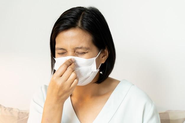 Vrouw die onder gezichtsmasker niest dat mond en neus behandelt terwijl het hoesten. corona virus of covid-19-concept.