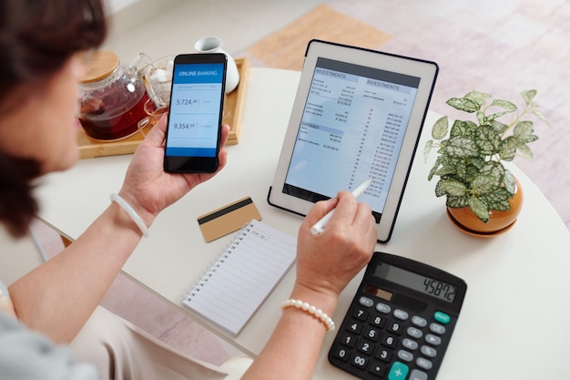 Vrouw die online bankieren gebruikt bij het controleren van haar effectenrekening op tabletcomputer