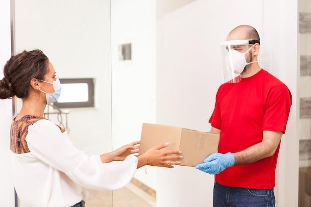 Vrouw die online bestelling opneemt bij bezorger die een beschermingsmasker draagt.