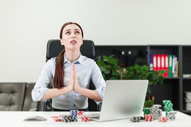 Vrouw die online casino en pook via laptop in het bureau speelt en bidt te winnen