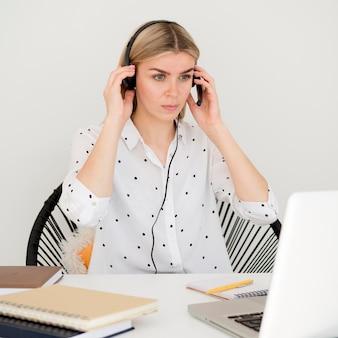 Vrouw die online cursussen bijwoont die hoofdtelefoons gebruiken