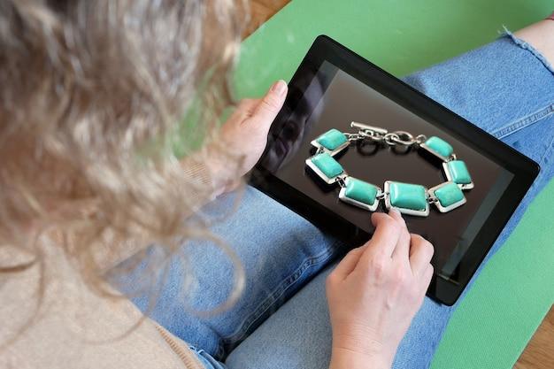 Vrouw die online voor douane winkelt in de internetwinkel van juwelen, close-up