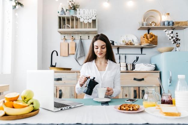 Vrouw die ontbijt heeft bij de keuken