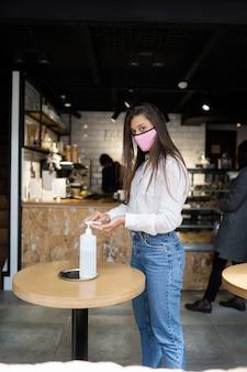 Vrouw die ontsmettingsgel gebruikt, reinigt de handen van het coronavirusvirus in het café