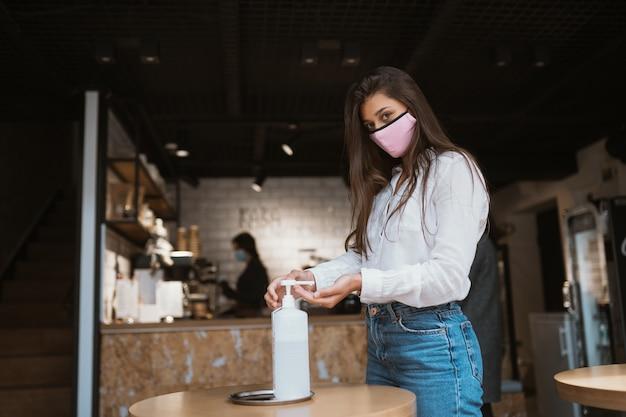 Vrouw die ontsmettingsgel gebruikt, reinigt de handen van het coronavirusvirus in het café.