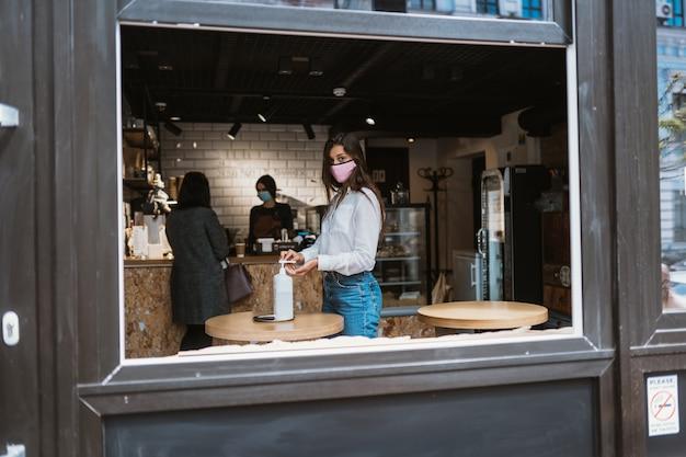 Vrouw die ontsmettingsgel gebruikt, reinigt handen van coronavirusvirus in café.