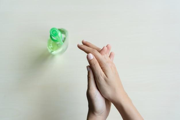 Vrouw die ontsmettingsmiddelgel op haar hand toepast voor bescherming tegen besmettelijke virussen, bacteriën en kiemen op houten achtergrond.