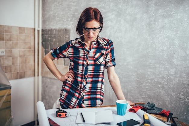 Vrouw die ontwerpplannen controleert een nieuwe keuken