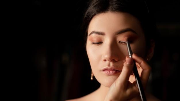Vrouw die oogschaduw aanbrengt. componeren. componeren. oogschaduw. borstel voor oogschaduw. make-up close-up ruimte voor tekst