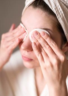 Vrouw die oogschaduw met micellair water verwijdert