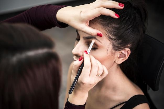 Vrouw die oogschaduw op model toepast