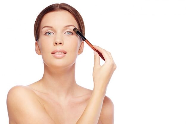Vrouw die oogschaduw op ooglid