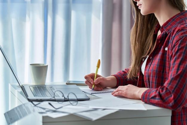 Vrouw die op afstand aan laptop werkt en belangrijke gegevensinformatie in notitieboekje neerschrijft. student tijdens afstandsonderwijs en online cursussen leren thuis